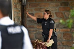 Detective Laura Lomeli of Anaheim Police Department's Sexual Assault Detail, knocks on a door, with her partner standing nearby, looking to check on a registered sex offender. Photo by Steven Georges/Behind the Badge OC